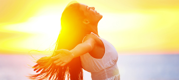 woman stretching arms in front of sunny sky